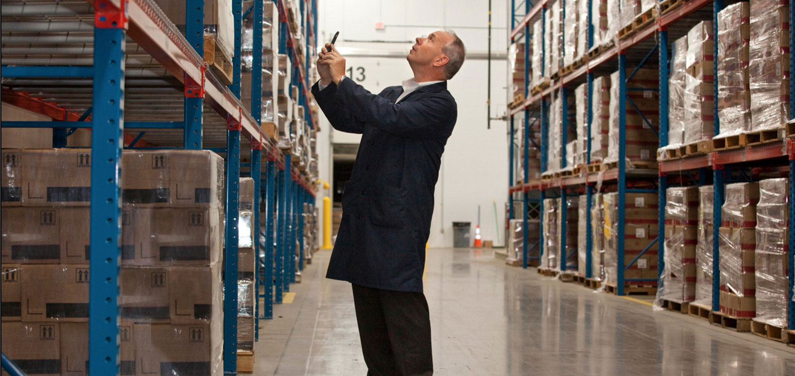 Business man taking picture in a warehouse